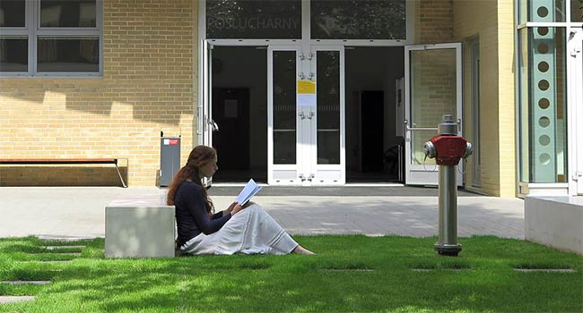 With a book on the lawn in front of Building D